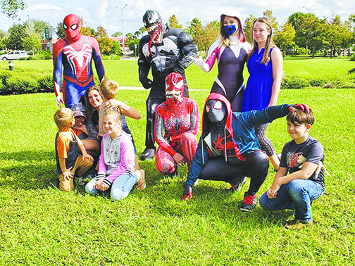 Johnathan Garcia and other volunteers dress up Saturday and take pictures with local children ahead of Halloween.