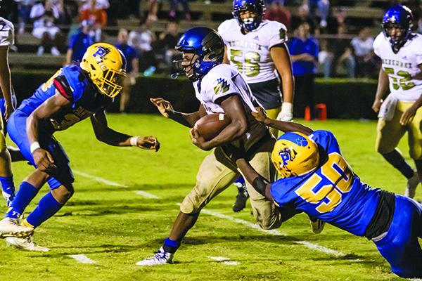 Palatka defenders David Williams (34) and Tyree Johns (50) combine for a stop of Menendez quarterback King Benford (11) in the second half of their Aug. 23 game. (FRAN RUCHALSKI / Palatka Daily News)