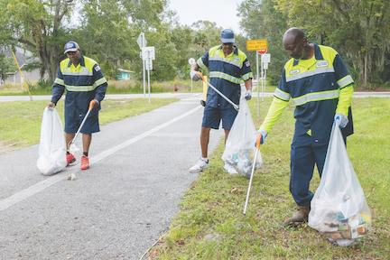Public Works employees pick up trash along a bike trail.