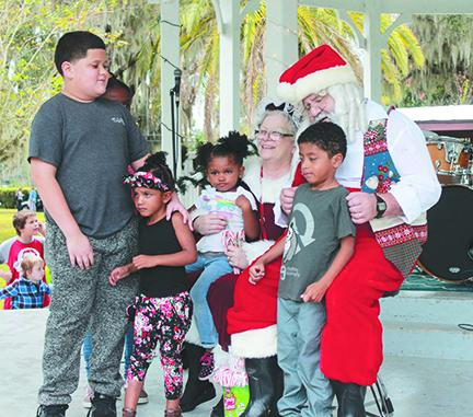 Children tell Santa and Mrs. Claus what they want for Christmas during last year's Christmas in the Park in Crescent City.
