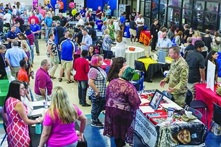 Students and their families talk with several businesses and college representatives at the Putnam County School District's College & Career Fair in August at Palatka High School. Workforce development is considered crucial to the county's future economic growth in retaining existing employers and recruiting new ones.