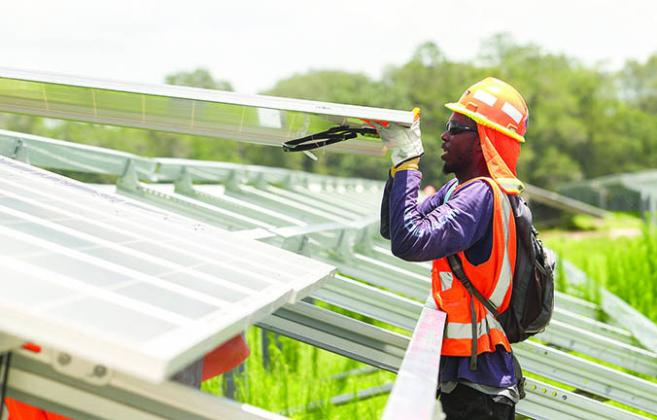 A worker with Florida Power & Light installs solar panels at the Horizon Solar Facility in Hawthorne.