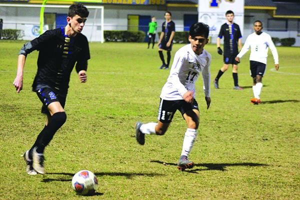 Michael Malota of Menendez is defended by Rodner Sales (17) of Palatka during the first half of Tuesday's District 3-4A tournament semifinal. (MARK BLUMENTHAL / Palatka Daily News)