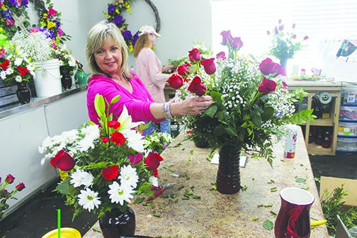 Flowers by Melanie owner Melanie Wells arranges a bouquet of red roses in a Valentine's Day arrangement Monday, beginning one of the busiest weeks of the year for her business. For a full story, see Page 5A.