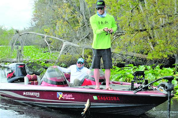 Byron Hendrix of Atlanta (standing) boats a bass on the final day of pre-fish, while flipping a jig in the lily pads. Brad Cassals (sitting) of Washington, D.C., is observing. (GREG WALKER / Special To The Daily News)