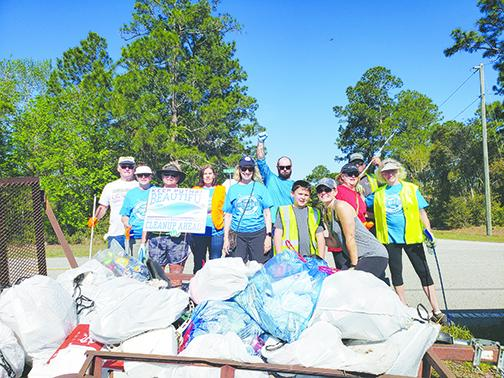 A group shows off their garbage collection from Keep Putnam Beautiful's Countywide Cleanup on Saturday along County Road 207A west of Hastings.