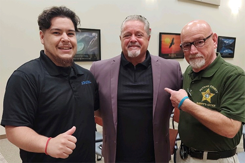Barry Stewart, center, the now former head of the Police Athletic League for the county, has a moment with the head of boxing at PAL, Faustino Garcia, left, and the new PAL leader, John Brady, during a ceremony last week.