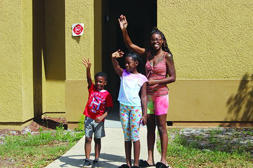 Darneshia Spell and her children, Ava Jones and Ty Jones, wave to Mellon Elementary School teachers as they pass to say hello to elementary school students the teachers have not forgotten about.