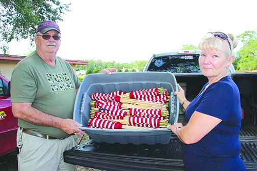 Volunteers Steve and Vicky Dennis unload American flags to be placed on veterans' graves at Oak Hill East and West cemeteries in Palatka on Thursday.