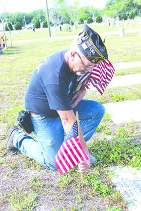 American Legion Bert Hodge Post 45 Commander Ken Moore places an American flag on a veteran's grave in Oak Hill West Cemetery in Palatka on Thursday.