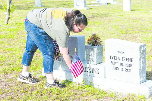 Robin Robinson, general manager of Christian radio station 91.3 Hope FM, places an American flag on a veteran's grave.