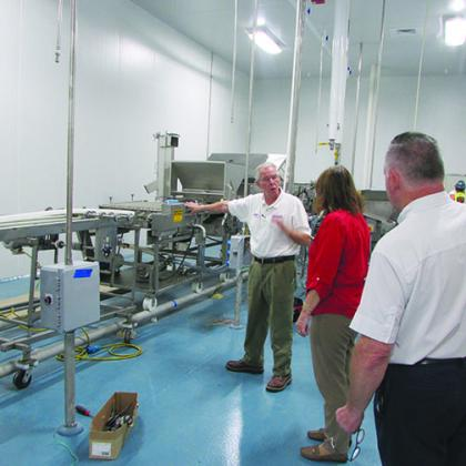Comarco Products officials show off the new plant.
