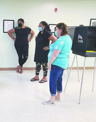 Election clerks Lisa Fells, Joann Vreen and Polly McCallum consider where to place another voting station while keeping it 6 feet away from the nearest station Friday at the Supervisor of Elections Office in Palatka.