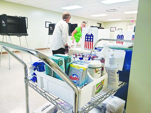 A cart filled with sanitizing products is stationed in the Supervisor of Elections Office on Friday while election clerks Claudia Wilkinson and Vicky Dennis set up for early voting.