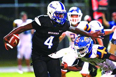 Interlachen High School quarterback Reggie Allen Jr. tries to avoid the tackle of Fernandina Beach's Sincere Rogers during Friday night's game. (GREG OYSTER / Special To The Daily News)