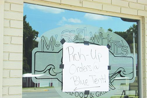 Musselwhite's in East Palatka posts a sign directing customers toward the pick-up area earlier this year when restaurants in Florida couldn't have indoor seating.
