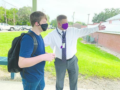 Miller Middle School Principal Tim Adams shows a student to class last month on the first day of school.