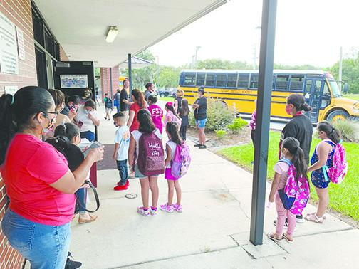 Workers at Middleton-Burney Elementary School assist students and parents last month during the first day of school, which was postponed by two weeks because of COVID-19 concerns.