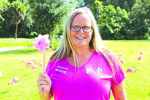 Mindy Estep, Pink Out Putnam committee director and member of the Woman's Club of Palatka, shows the pink pinwheels club members were putting on the lawn at the woman's club, along with pink flamingos, in observance of October being National Breast Cancer awareness month.