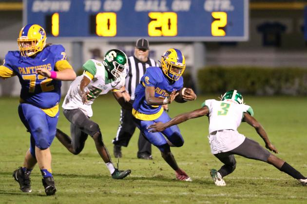 Palatka High School quarterback O'marrion Wilson tries to get past Live Oak Suwannee High would-be tacklers Keyshawn Jones (9) and Keiwan Ladler during Friday night's game at home. (GREG OYSTER / Special To The Daily News)
