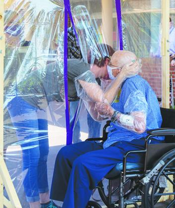 Julie Byers hugs her grandfather, Burcell Donoho, through a plastic protective barrier Friday after not being able to see him for months because of coronavirus precautions.
