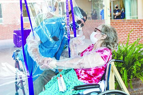William Hines leans in as close as possible to his wife, Ann Hines, on Friday at Windsor Care and Rehab in Palatka.