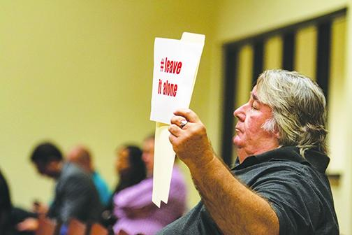 Seber Newsome III holds up a sign during Tuesday's Board of County Commission meeting advocating leaving the controversial Confederate monument at the Putnam County Courthouse.