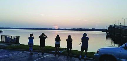 Morning Maniacs members watch the sunrise before they jog and clean up Memorial Bridge in Palatka earlier this year.