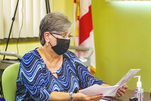 Judge Libby Morris analyzes a mail ballot Friday to check its validity during a Canvassing Board meeting in the Supervisor of Elections Office in Palatka.