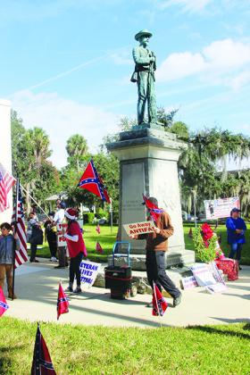 Protesters advocate for the Confederate statue remaining on the Putnam County Courthouse lawn during a protest Saturday at the courthouse.