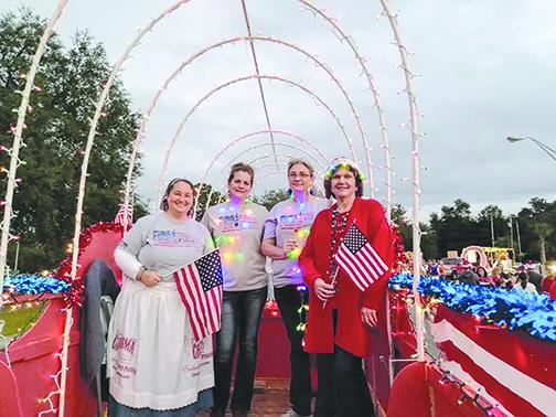 Amy Stanley, Leigh Hand, Carissa Williams and Marcy Lee smile on the Melrose Patriots parade float Saturday at Bonnie Melrose Christmas Parade of Lights.