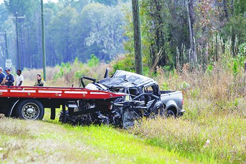 A crushed pickup truck on the side of State Road 100 is loaded onto a tow truck Wednesday after its driver collided with a tractor-trailer that morning.