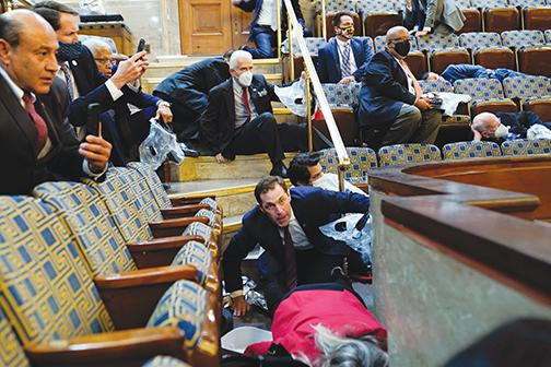 People shelter in the House gallery as protesters try to break into the House Chamber at the U.S. Capitol on Wednesday in Washington.