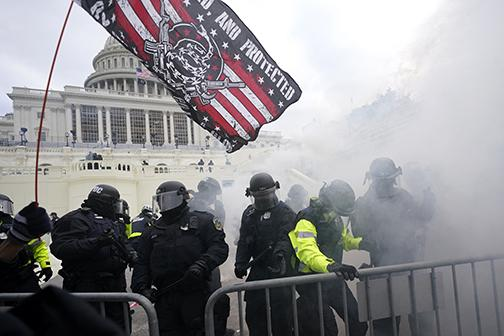 Police hold off President Donald Trump supporters who tried to break through a police barrier Wednesday at the Capitol in Washington. As Congress prepared to affirm President-elect Joe Biden's victory, thousands of people gathered to show their support for Trump and his claims of election fraud.
