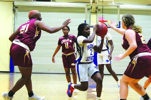Palatka's Zyria Jones goes between North Marion's Jermaya Jackson (21) and Sophie Watson (right) during Monday night's game. (MARK BLUMENTHAL / Palatka Daily News)