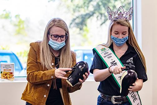 Samantha Harper, the 2020 National Teen Miss Agriculture USA, peels an eggplant with her mom, Abby Houser, on Thursday at Comarco Products in Palatka.