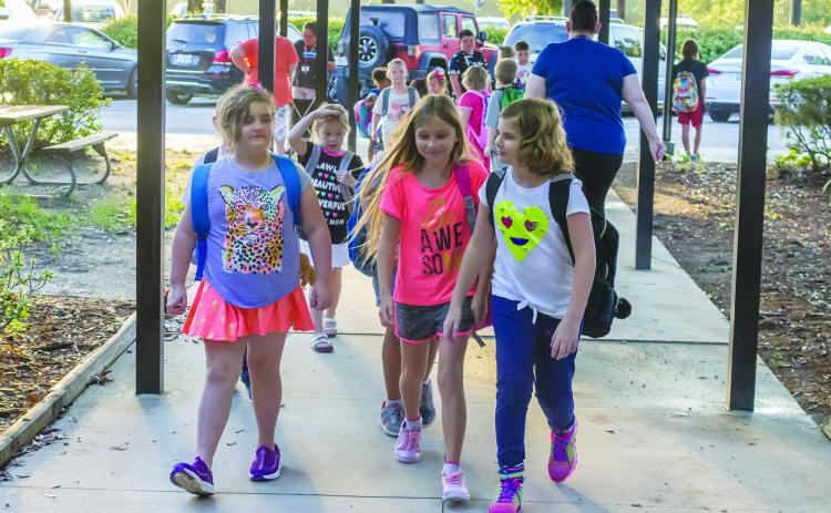 Students walk into Interlachen Elementary School on Monday morning on their first day of school.