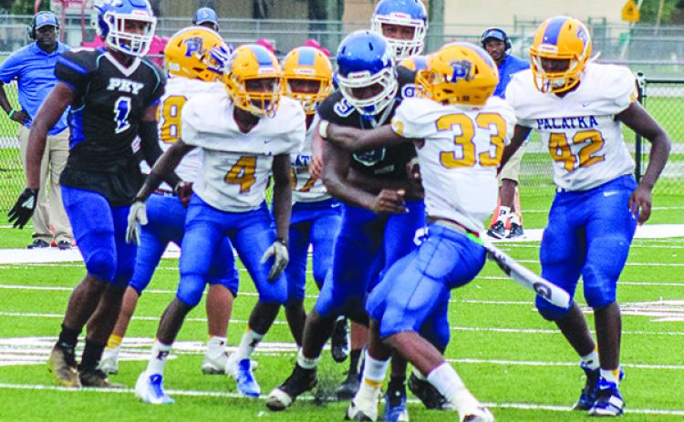 P.K. Yonge quarterback Jontez Williams churns for yards while Palatka defenders, most notably Shemar Curry (33), try to take him down during Saturday's game at Bradford High School. (ANDY HALL / Palatka Daily News)