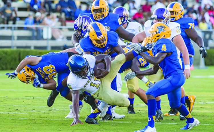 A host of Panthers upend Menendez quarterback King Benford in the first half of their game last Friday night. (FRAN RUCHALSKI / Palatka Daily News)