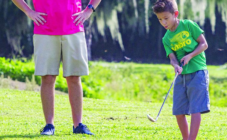 Under the watchful eye of instructor Troy Sheffield, eight-year-old Ely Watson tries his hand at a golf clinic last summer. The City of Palatka Recreation Department is holding six weeks of beginner youth golf lessons. For details, call 983-1254. (Daily News file photo)