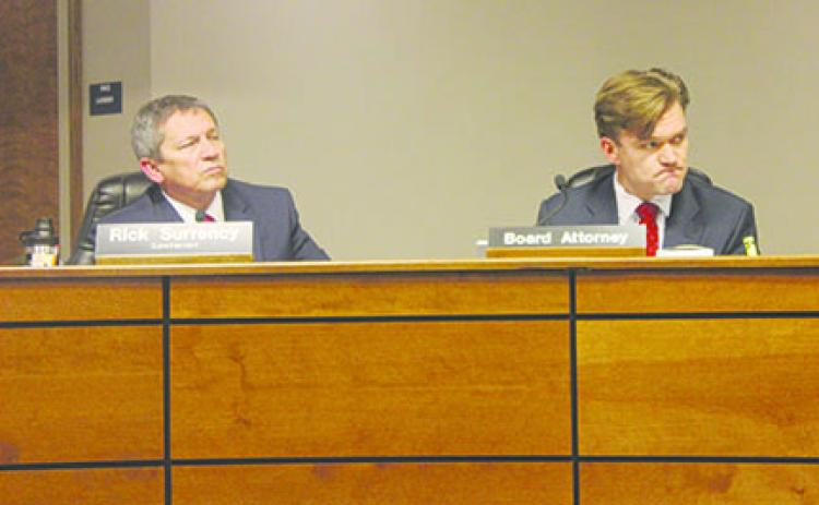 Superintendent Rick Surrency and attorney Jett Baumann listen to matters at Tuesday's Putnam County School District board meeting.