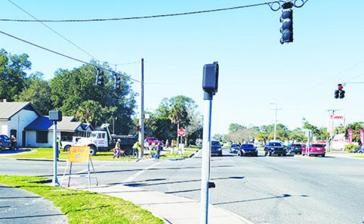 Construction crews work on the sidewalk at the intersection of Crill and Palm avenues on Tuesday morning.