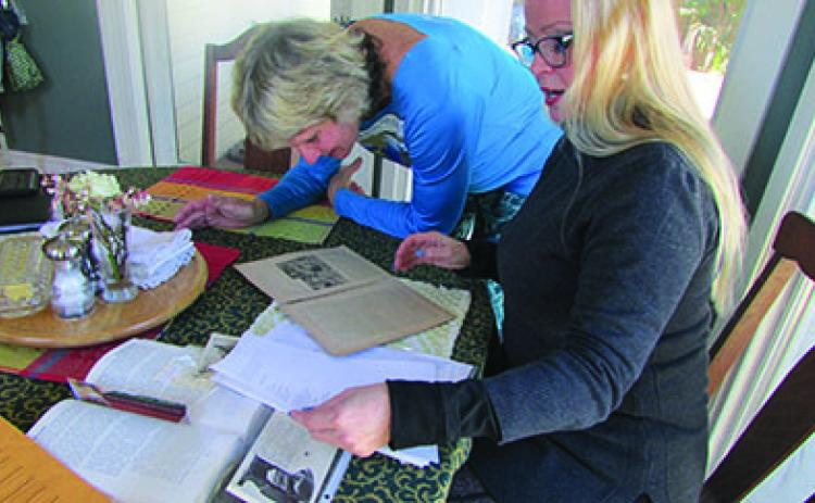 Lydia Bartram, right, shows some family artifacts to Linda Crider at the Bartram Inn in Palatka.