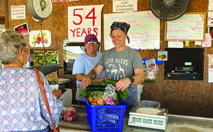 Toree Ashe rings up a customer Tuesday while Dawn Brown helps at County Line Produce Stand.