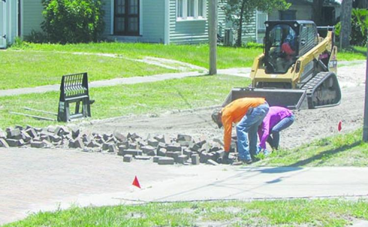 Contruction workers collect bricks from Hotel Street in Palatka.
