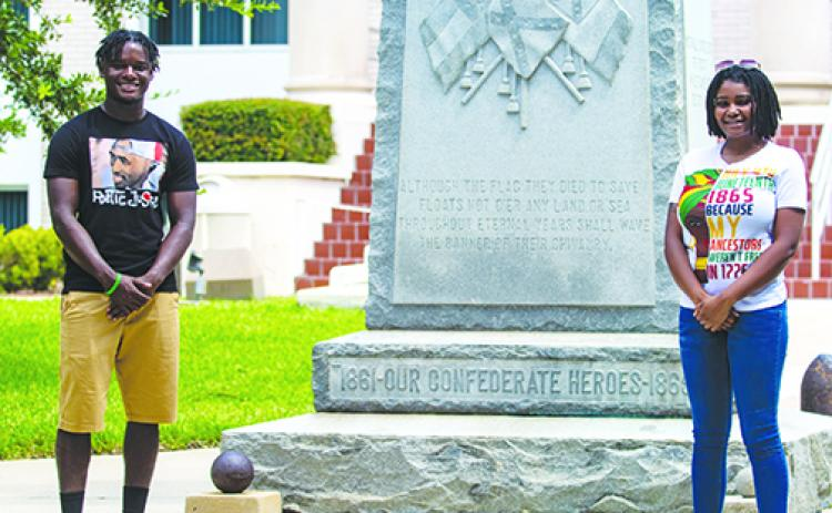 Protest organizers Tevel Adams and Dar'Nesha Leonard stand in front of the Confederate statue at the Putnam County Courthouse on Thursday.