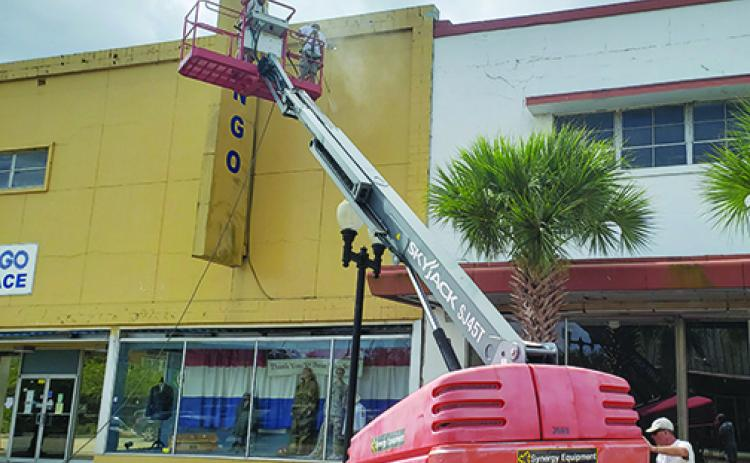 Workers prepare the old JCPenney building in downtown Palatka for a new coat of paint.