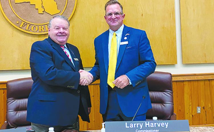 Previous and current Board of County Commissioners chairmen Terry Turner and Larry Harvey shake hands after the transition.