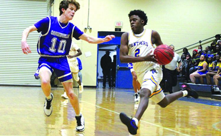 Palatka High School's Vanari Johnson (right) takes the ball to the basket against Gainesville High's Cal Evans during Tuesday night's game. (MARK BLUMENTHAL / Palatka Daily News)