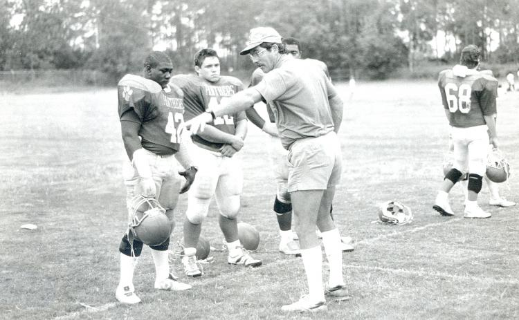 Palatka High line coach Tony Alred makes his point to linemen Darrell Polite, left, David Hudson and Joel Walker (behind) during a 1989 practice. Alred passed away Friday at the age of 75. (Daily News file photo)